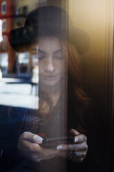 Young woman behind window pane looking at cell phone - GIOF000544
