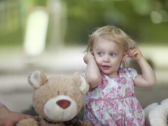 Portrait of blond little girl sitting besides her teddy bear - NIF000050