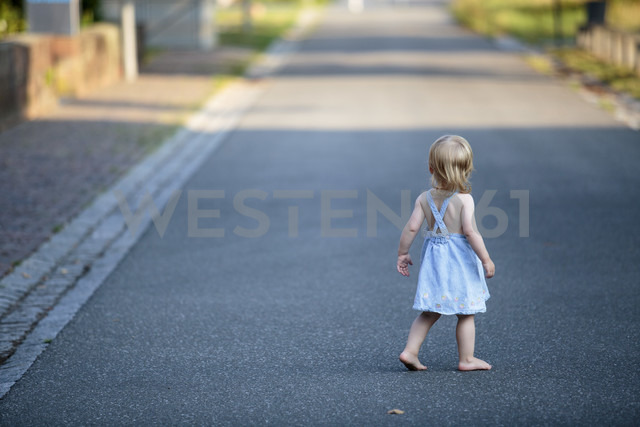 Back view of barefoot blond little girl walking on empty road - NIF000062 - Nailia Schwarz/Westend61