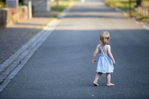 Back view of barefoot blond little girl walking on empty road - NIF000062