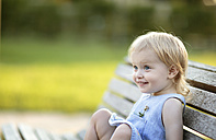 Portrait of smiling blond little girl sitting on park bench - NIF000065