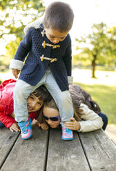 Three children playing together in a park - MGOF001055