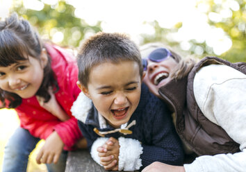 Three laughing children playing together in a park - MGOF001058