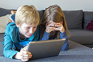 Boy and girl lying on the couch using digital tablet - SARF002311