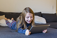 Smiling girl lying on the couch using digital tablet - SARF002314