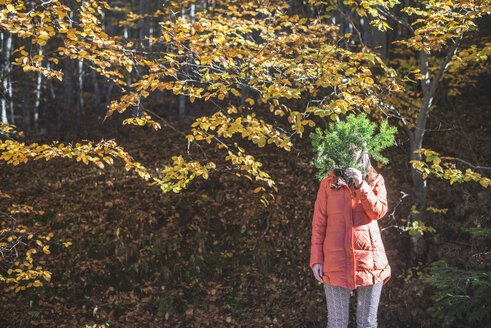 Woman hiding her face behind fir branch in autumnal forest - DEGF000586