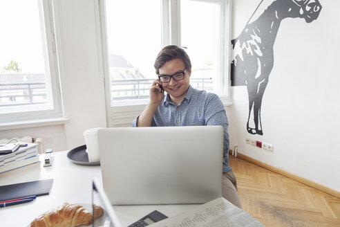 Smiling young businesssman with laptop and cell phone in a modern office - JUBF000062