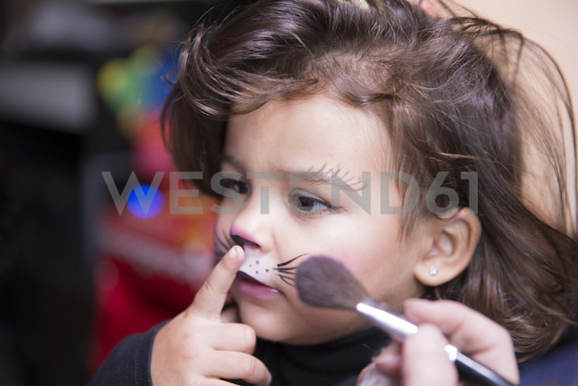 Woman painting little girl's face like a cat - ERLF000081 - Enrique Ramos/Westend61
