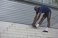 Athlete doing stretching exercises on stairs - MADF000615
