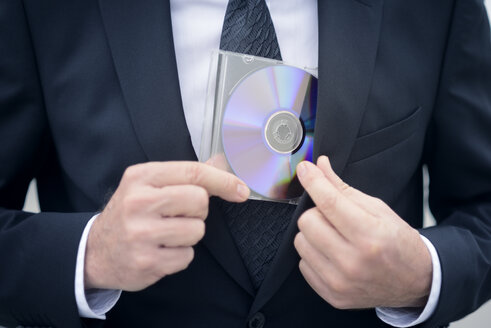 Businessman with data dvd, data theft - GUFF000167