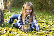 Portrait of smiling little girl lying on a meadow in the garden with her tabby cat - YFF000476
