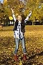 Happy little girl throwing autumn leaves while jumping in the air - YFF000479