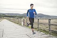 Spain, Ferrol, jogger running on a boardwalk - RAEF000672