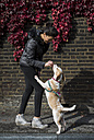 UK, London, woman rewarding her dog - MAUF000042