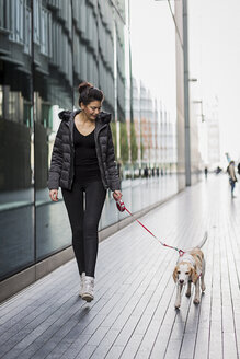UK, London, woman and her dog walking on pavement in the city - MAUF000051