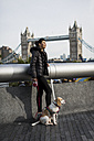 UK, London, woman and her dog relaxing in the city - MAUF000054