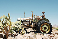 Namibia, Namib desert, Man driving an abandoned old tractor in Solitaire - GEMF000494
