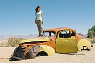 Namibia, Namib desert, Woman standing on an abandoned car in Solitaire - GEMF000497
