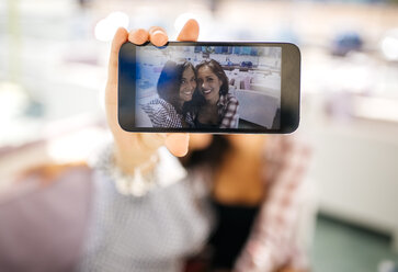 Selfie of two smiling female friends on cell phone display - MGOF001069
