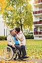 Senior woman kissing husband in wheelchair - UUF006110