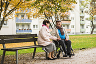 Senior woman sitting on bench next to husband in wheelchair - UUF006116