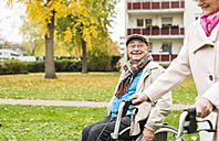 Senior woman with wheeled walker and senior man in wheelchair outdoors in autumn - UUF006125