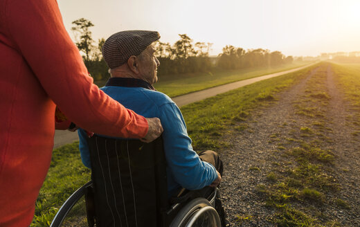 Senior woman pushing husband in wheelchair in the nature - UUF006146
