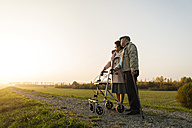 Senior couple with walking stick and wheeled walker standing in the nature - UUF006158