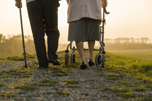 Senior couple walking with walking stick and wheeled walker in the nature - UUF006161