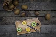 Green and golden kiwis on chopping board, wood - LVF004171