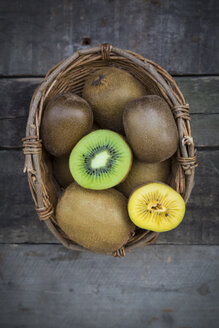Green and golden kiwis, basket on wood - LVF004177