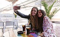 Two female friends taking a selfie with smartphone in a cafe - MGOF001077