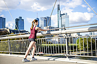 Germany, Frankfurt, young athlete stretching on bridge - PUF000438