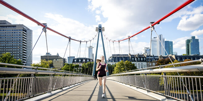 Germany, Frankfurt, young woman jogging on bridge - PUF000441