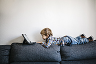 Little boy lying on backrest of a couch looking at digital tablet - JRFF000200