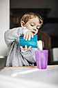 Portrait of little boy playing with cups and water - JRFF000209