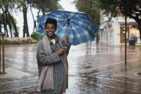 Italy, Grado, smiling woman with umbrella on a rainy day in autumn - MAUF000061