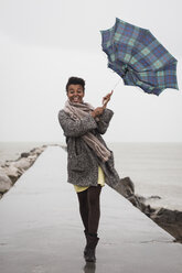 Italy, Grado, woman holding umbrella on a rainy day in front of the sea - MAUF000067