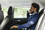 Smiling businessman sitting on back seat of a car telephoning with smartphone - EBSF001138