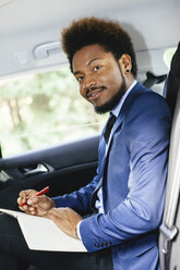 Portrait of businessman sitting on back seat of a car writing down something - EBSF001144