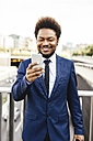 Portrait of smiling businessman  looking at his smartphone - EBSF001150