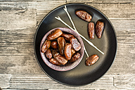 Bowl of dates, skewers and plate on wood - SARF002319