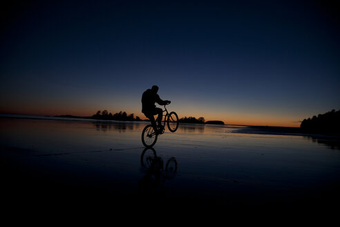 Canada, Vancouver Island, Longbeach, Man biking at the beach - TM000063