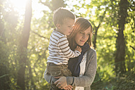 Mother with little son on her arms at backlight - PAF001482