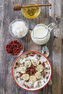 Bowl of muesli with banana slices, chia seeds, coconut chips and goji berries - SARF002326