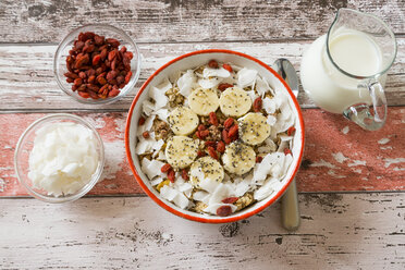 Bowl of muesli with banana slices, chia seeds, coconut chips and goji berries - SARF002329