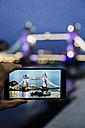 UK, London, man's hand holding smartphone with photo of Tower Bridge at twilight - MAUF000078