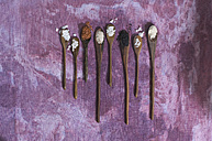 Row of wooden spoons with different salts on cloth - ASF005766