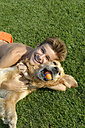 Teenage boy playing with Golden Retriever on lawn - LBF001287