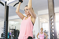 Woman doing pull-ups in gym - MADF000724